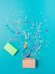 Pink gift box with various party confetti, streamers, noisemakers and decoration on a blue background. Colorful celebration concept.