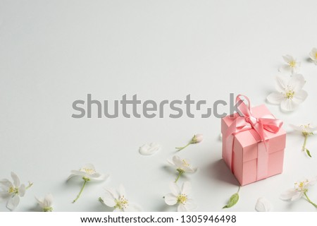 pink gift surrounded by Apple flowers. gentle background, copy space. present for mother's day, spring, Valentine's day, women's day. #1305946498