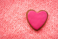 pink gingerbread in shape of heart on a background of pink knitted fabric