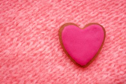 pink gingerbread in shape of heart on pink knitted background