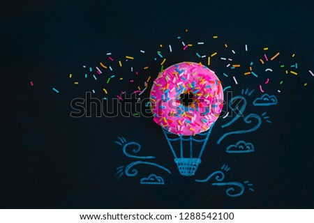 Pink glazed donut with chalk drawing of a hot air balloon. Creative concept. Flat lay food photography. Foto stock ©