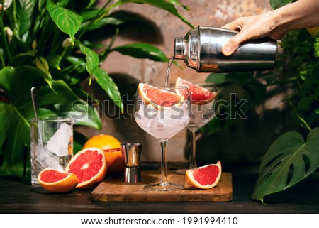 Pink grapefruit and rosemary gin cocktail  poured in prepared gin cocktail glass on a tropical beach bar