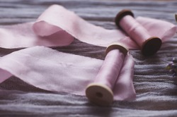 pink handmade textile ribbon wound on bobbins lies on a wooden table