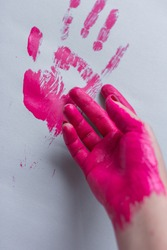 Pink handprint  and painted hand on grey paper