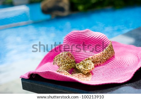 pink hat on table nearby the brink of pool.