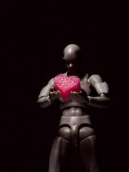 Pink heart being held by synthetic hands of humanoid robot in shadows defocused. Artificial intelligence concept.