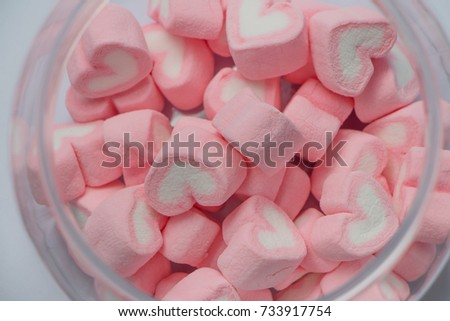 Pink heart candy closeup in a jar for sweet love theme and Valentine background. Beautiful pink heart, pink heart in a blurred jar. #733917754