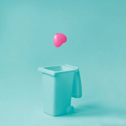 Pink heart falling in garbage bean against pastel blue background. Broken, fake, lost love. Minimal relationship concept.