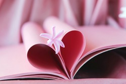 Pink heart from book pages, fresh flower, emotion of love, background for romantic congratulation, postcard