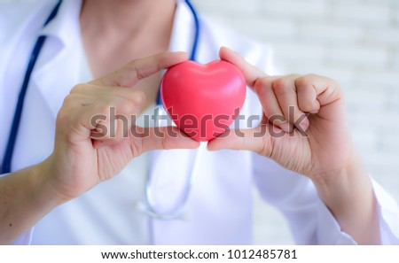 Pink Heart in the hands of the doctor who mediates health. Pink heart that expresses love and concern. Women holding the pink heart. Valentine's Day. Love concept. Health concept. selective focus.