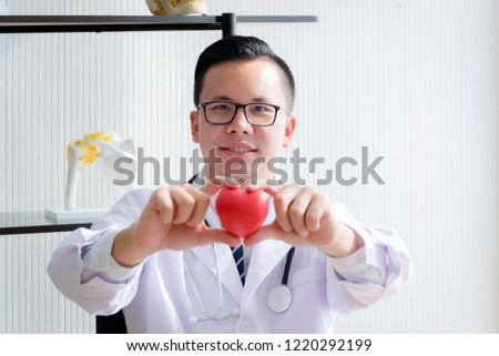 Pink Heart in the hands of the doctor who mediates health. Pink heart that expresses love and concern. Man holding the pink heart. Valentine's Day. Love concept. Health concept. selective focus. #1220292199