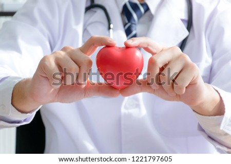 Pink Heart in the hands of the doctor who mediates health. Pink heart that expresses love and concern. Man holding the pink heart. Valentine's Day. Love concept. Health concept. selective focus. #1221797605