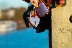 Pink heart padlock between different padlocks at the bridge . Frankfurt Eiserner Steg, padlocks attached to the bridge railing.