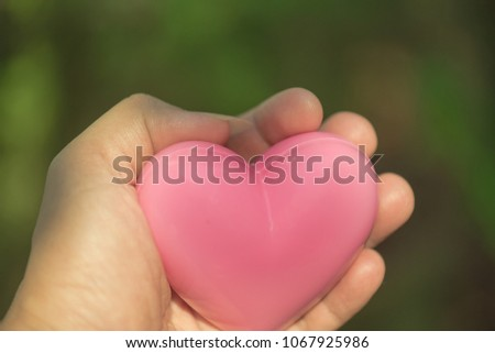 Pink heart shape in hand. #1067925986