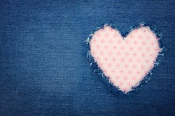Pink heart shape torn from blue denim jeans fabric with copy space, romantic love concept background