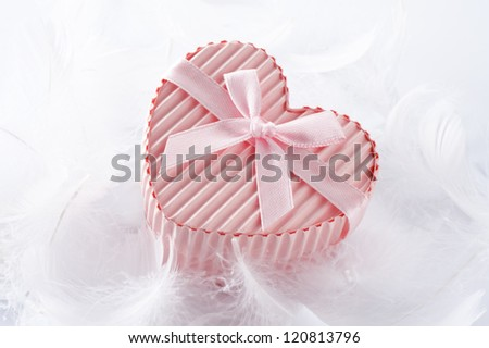 Pink heart shaped gift box with ribbon  white bird feather background