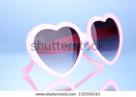 Pink heart-shaped sunglasses on blue background