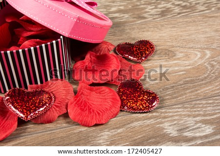 pink Heart shaped Valentines Day gift box with rose petals on old wood