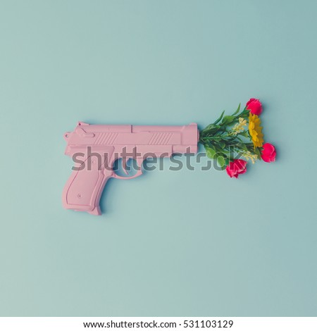 Pink hipster handgun on blue pastel background with flowers. Piece flat lay concept.