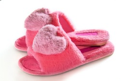 Pink homemade fluffy slippers with a heart isolated on a white background. Gift for Valentine's Day.