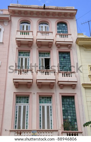 Pink house with balconies and stained glass in Havana backstreet