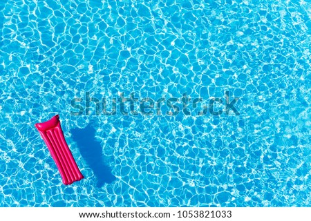 Pink inflatable mattress floating on water surface #1053821033