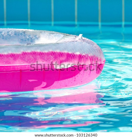 Pink inflatable round tube in swimming pool