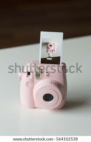 Pink Instant Camera with Film Coming Out Showing Shot of Camera