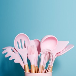 Pink kitchen utensils on blue background, home kitchen tools decor concept, rubber accessories in container. Restaurant, cooking, culinary, kitchen theme. Silicone spatulas and brushes with copyspace