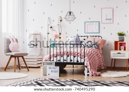 Pink knit blanket on girl's bed with pillows in colorful bedroom with ladder, chair and plant #740495290