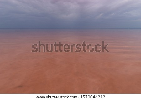 Pink Lake Elton with clouds, in cloudy weather but without wind and smooth smooth water