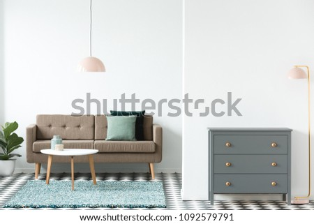 Pink lamp next to grey cabinet in retro living room interior with white table on rug near brown sofa