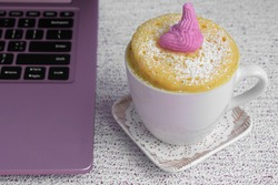 pink laptop. A cupcake in a mug is on a saucer. The concept of a quick snack for lunch. Microwave Vanilla Cupcake. High quality photo