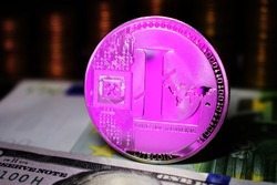 Pink Litecoin LTC coin is surrounded by a money background.