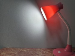 pink luminous desk lamp on the table near wall with beam of light.