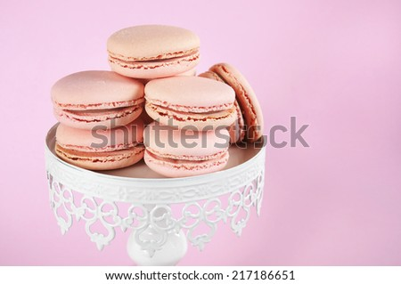 Pink macarons on white vintage style cake stand against pale pink background.