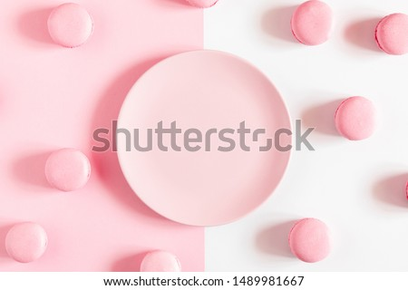 Pink macaroons, empty pink plate on pink and white background. Sweet background. Flat lay, top view, copy space