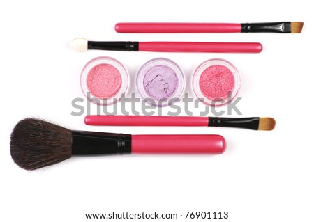 Pink make-up brushes and powder eye shadows in jars isolated on white background.