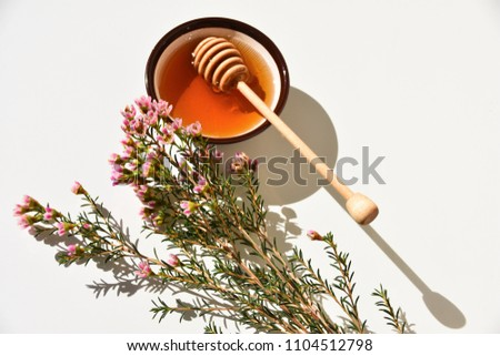Pink manuka tree flower and manuka honey in a bowl, on a white background. Close up.