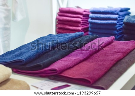 Pink, maroon, purple, black fluffy towels for beauty and SPA salon. Pile of towels in a beauty store #1193299657