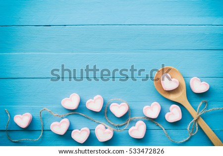 Pink marshmallow in heart shape stacked on blue wood table with copy space. Sweet candy for love theme on Valentine concept in vintage style. Pastel color dessert for background or wallpaper decor.