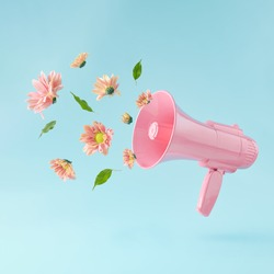 Pink megaphone with colorful summer flowers and green leaves against pastel blue background. Advertisement idea. Minimal nature concept.