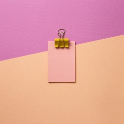 Pink memo paper, sticky notes with yellow binder clip on pink background. top view, copy space