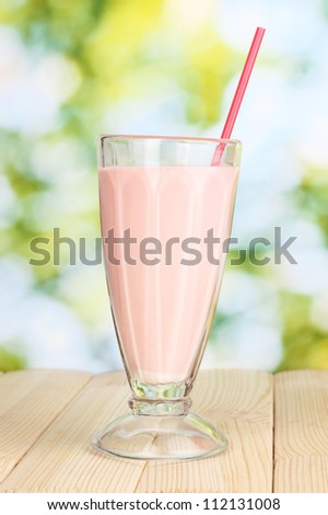 Pink milk shake on wooden table on bright background