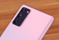 Pink Mobile phone with three cameras on wooden background