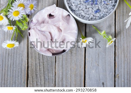 pink moisturizer cream, blue bath salt and white flowers on natural rusty wood table
