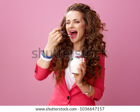 Pink Mood. Portrait of happy young woman with long wavy brunette hair isolated on pink eating farm organic yogurt #1036647157