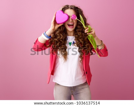 Pink Mood. smiling stylish woman with long wavy brunette hair isolated on pink background hiding behind a flower and heart shaped box of chocolates #1036137514