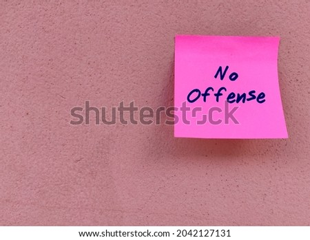 Pink note on copy space wall with text written NO OFFENSE to indicate the listener not to feel hurt, angry, or upset by what is about to be saidalthough it may seem rather rude. Foto stock ©
