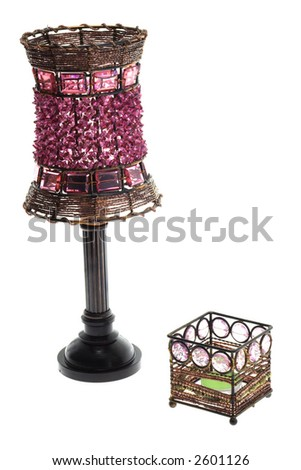 Pink old lamp next to a candle